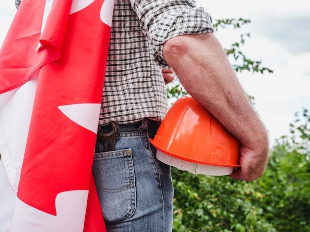 Uomo attraente che tiene una bandiera canadese su cielo blu in una giornata limpida e soleggiata. vista da dietro, primo piano. concetto di festa nazionale