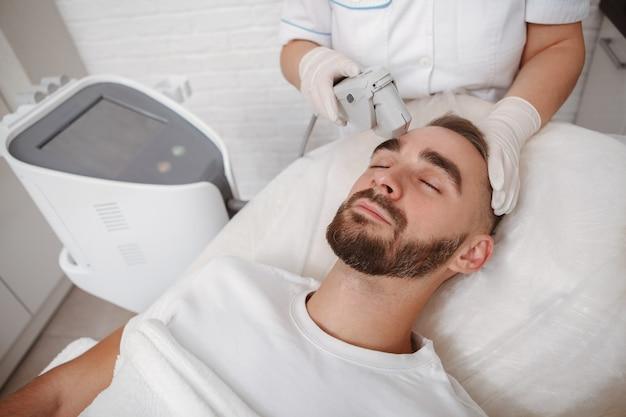 Uomo attraente che si distende mentre ottiene un trattamento di cura della pelle dall'estetista