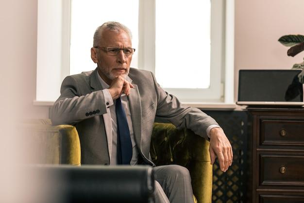 Uomo attraente. ritratto in vita di un bell'uomo dai capelli grigi seduto in una poltrona verde oliva mentre guarda fisso in lontananza