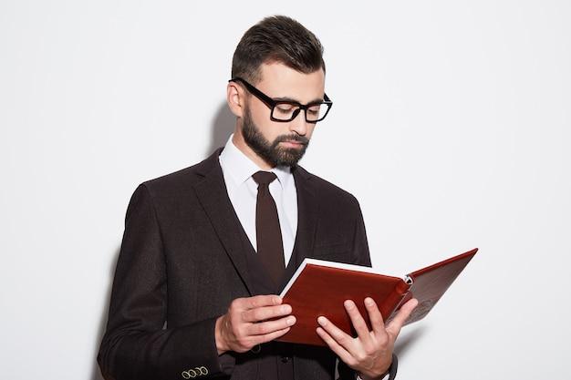 Uomo attraente con barba e capelli neri che indossa una camicia bianca con cravatta, abito nero e occhiali da sole a sfondo bianco studio, ritratto, che tiene un libro.