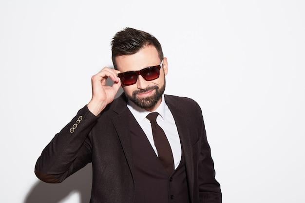 Uomo attraente con barba e capelli neri che indossa una camicia bianca con cravatta, abito nero e occhiali da sole a sfondo bianco studio, ritratto, che guarda l'obbiettivo.