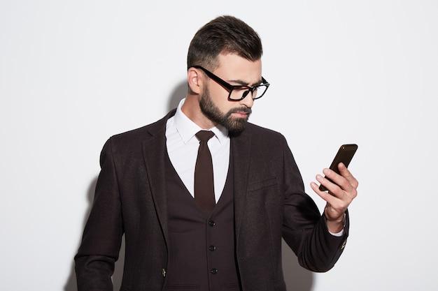 Uomo attraente con barba e capelli neri che indossa una camicia bianca con cravatta, abito nero e occhiali da sole a sfondo bianco studio, ritratto, guardando il telefono cellulare.