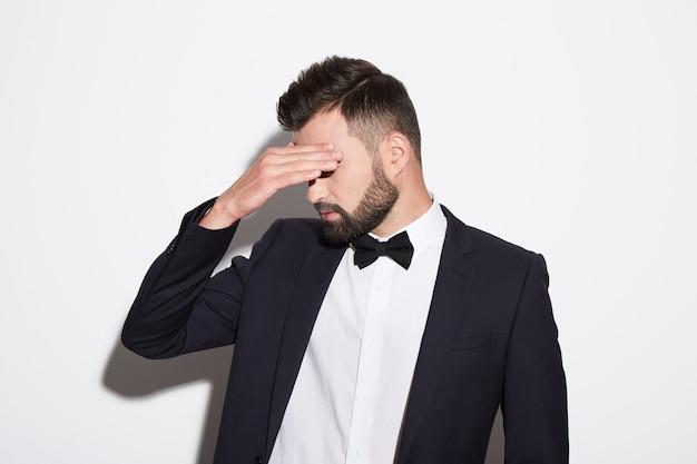 Uomo attraente con barba e capelli neri che indossa una camicia bianca con cravatta, abito nero e occhiali da sole a sfondo bianco studio, ritratto, posa, posa facepalm.