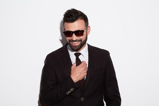 Uomo attraente con barba e capelli neri che indossa una camicia bianca con cravatta, abito nero e occhiali da sole a sfondo bianco studio, ritratto, in posa.