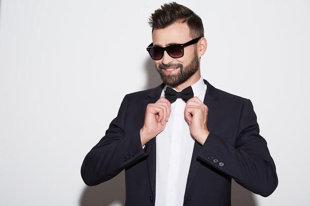 Uomo attraente con barba e capelli neri che indossa una camicia bianca con cravatta, abito nero e occhiali da sole a sfondo bianco studio, ritratto, sorridente.