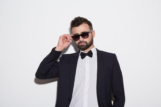 Uomo attraente con barba e capelli neri che indossa una camicia bianca con cravatta, abito nero e occhiali da sole a sfondo bianco studio, ritratto.
