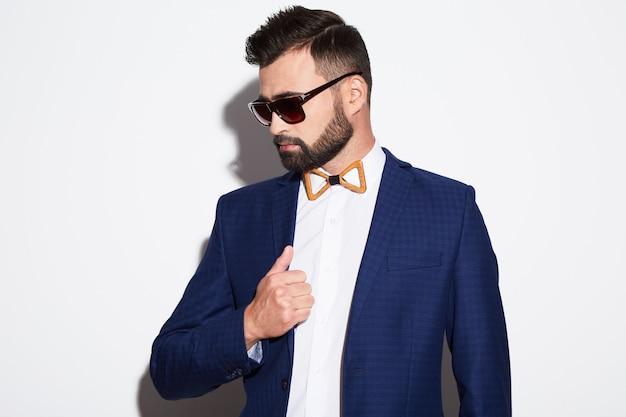 Uomo attraente con capelli neri e barba che indossa camicia bianca con cravatta a farfalla, abito blu e occhiali da sole a sfondo bianco studio, ritratto, in posa.