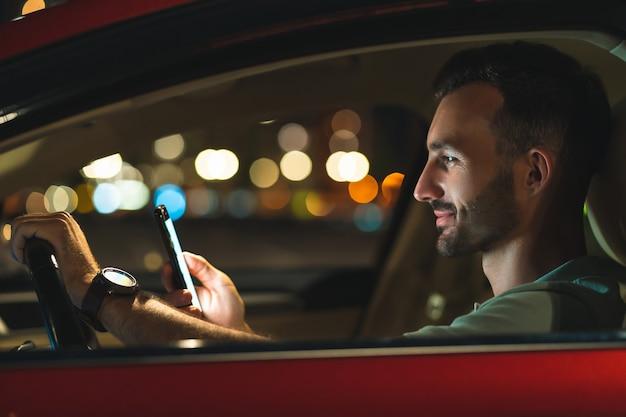 L'uomo attraente con lo smartphone seduto in macchina
