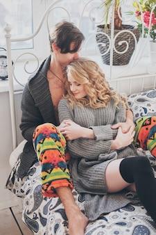 Uomo attraente e donna in camera da letto insieme coccole carino