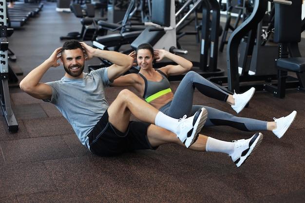 Attraente uomo e donna che lavorano in coppia eseguendo sit up in palestra.