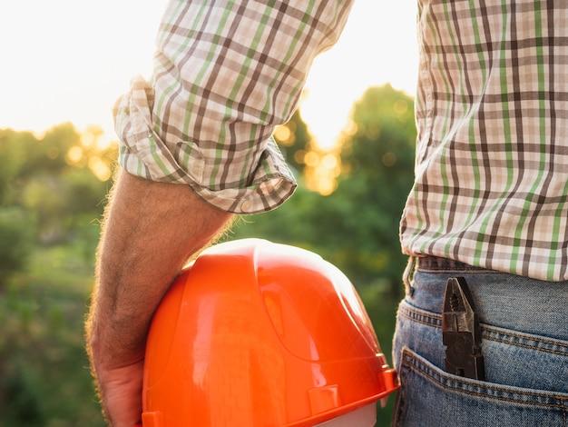 Uomo attraente in abiti da lavoro, con in mano gli strumenti sullo sfondo di alberi, cielo azzurro e tramonto. vista dal retro. concetto di lavoro e occupazione