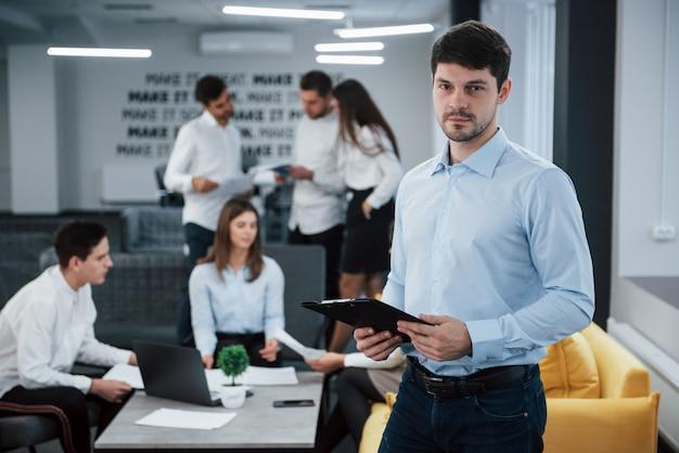 Manager attraente pronto a rispondere alle tue domande. il ritratto di giovane tipo sta nell'ufficio con gli impiegati a fondo