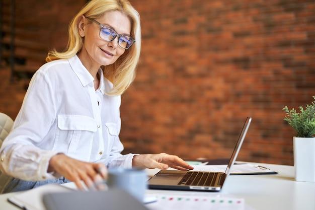 Attraente imprenditrice matura con gli occhiali che usa il laptop e fa alcune scartoffie in ufficio