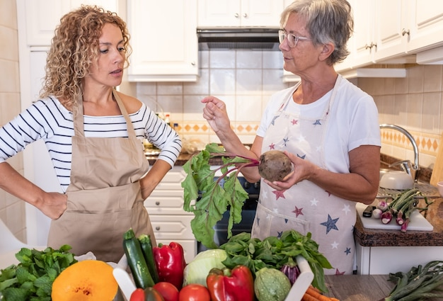 Attraente donna riccia matura nella cucina di casa con sua madre che ascolta i consigli per preparare le verdure. crudo fresco raccolto in tavola