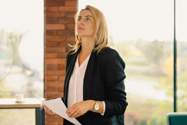 Mentore attraente, giovane donna sicura in abbigliamento formale che tiene i documenti pensieroso che osserva in su.
