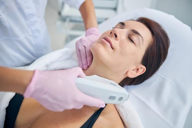 Attraente cliente di mezza età che si appisola durante una procedura di rassodamento della pelle condotta da un dermatologo