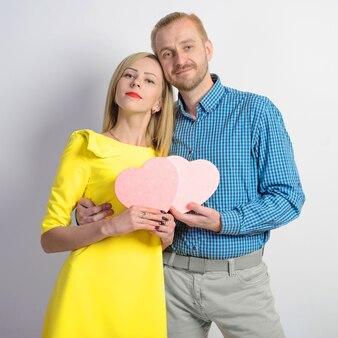 Un uomo di mezza età attraente in una camicia a quadri e una ragazza snella in un vestito giallo sta tenendo un cuore rosa. bella coppia in studio. amarsi l'un l'altro