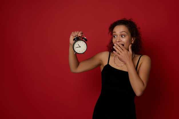 Attraente donna di razza mista vestita in abito da sera nero si copre la bocca guardando una sveglia in mano, isolata su sfondo rosso con spazio di copia. felice anno nuovo e concetto di natale