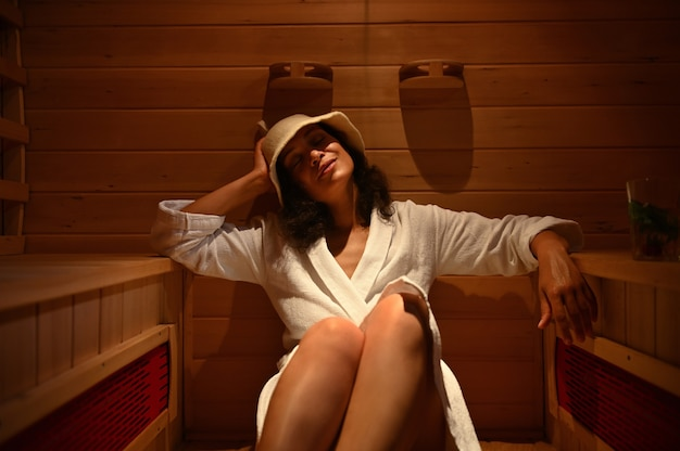 Attraente donna di razza mista nella sauna, godendosi la cottura a vapore.