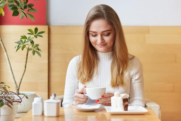 Modello attraente si siede sulla sedia e guarda in tazza di caffè. sognando la ragazza con i capelli biondi indossa un abito bianco, tiene la tazza in due mani