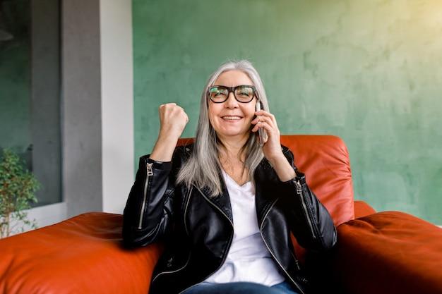 Attraente signora senior moderna in giacca di pelle nera, seduta in morbida poltrona rossa, tenendo il pugno chiuso e sorridente durante la chiamata mobile