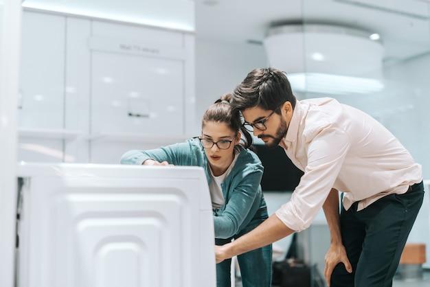 Attraente coppia multiculturale guardando la nuova lavatrice che vogliono acquistare