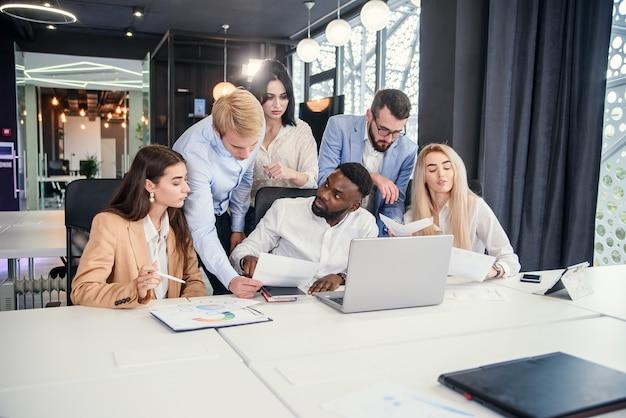 Attraenti gestori di uffici multirazziali che discutono il loro piano aziendale sul personal computer e analizzano i problemi.