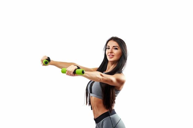 Attraente donna fitness muscolare facendo esercizi utilizzando manubri. ritratto su uno sfondo bianco