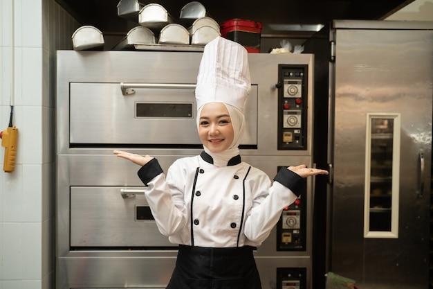 Attraente donna musulmana baker sorride alla telecamera nella cucina del panificio con grande forno