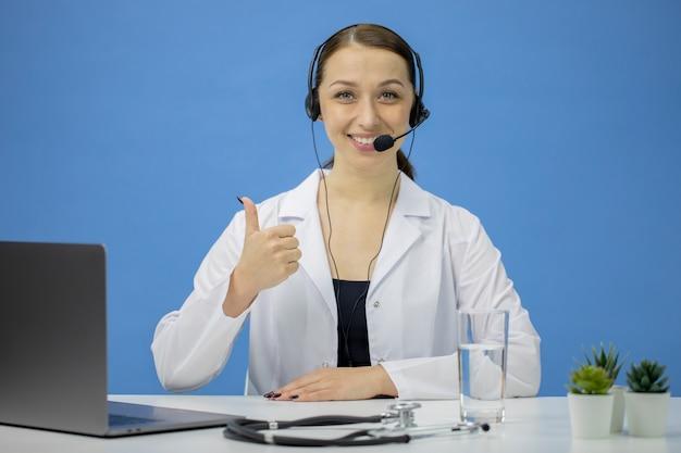 Consulente online attraente in camice e cuffie che mostrano come segno