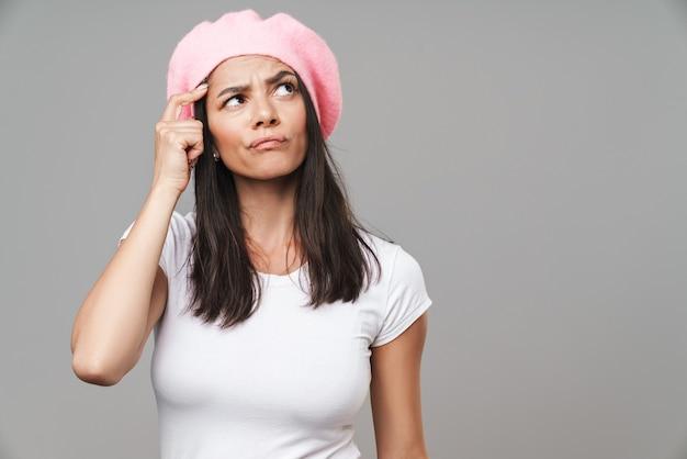 Attraente giovane donna bruna pensierosa che indossa un berretto in piedi isolato su un muro grigio