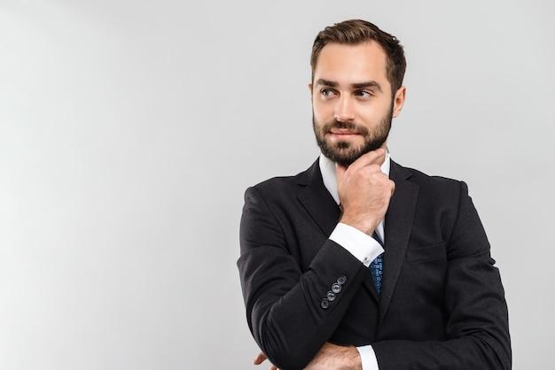 Attraente giovane uomo d'affari pensieroso che indossa un abito in piedi isolato su un muro grigio