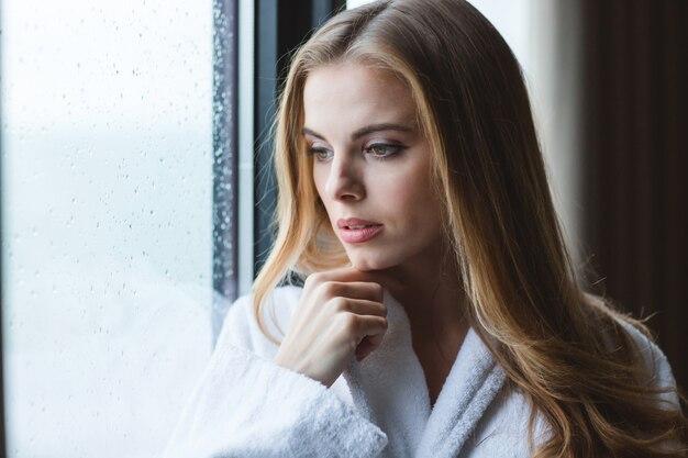 Attraente giovane donna pensierosa in accappatoio bianco che guarda fuori dalla finestra