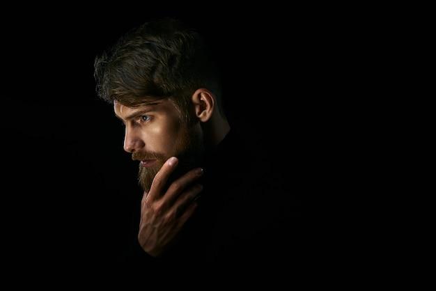 Attraente giovane pensieroso guarda in lontananza accarezzandosi la barba su sfondo nero