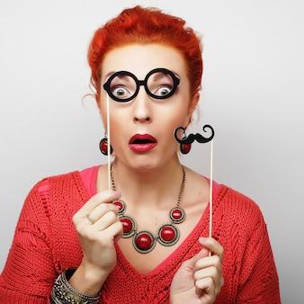 Attraente giovane donna allegra che tiene i baffi e gli occhiali su un bastone. pronto per la festa.