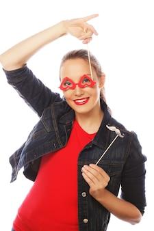 Attraente giovane donna giocosa tenendo i baffi e occhiali su un bastone. pronto per la festa.