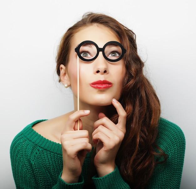 Attraente giovane donna giocosa con occhiali finti, pronta per la festa