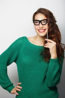 Attraente giovane donna giocosa con occhiali falsi