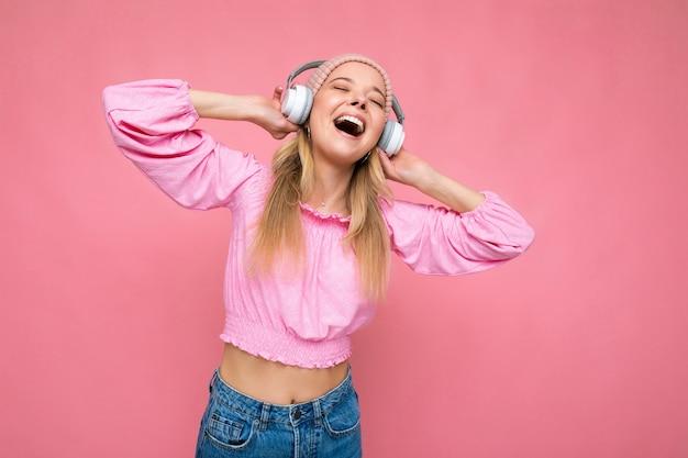 Attraente giovane donna bionda sorridente emotiva positiva che indossa una camicetta rosa e un cappello rosa isolato