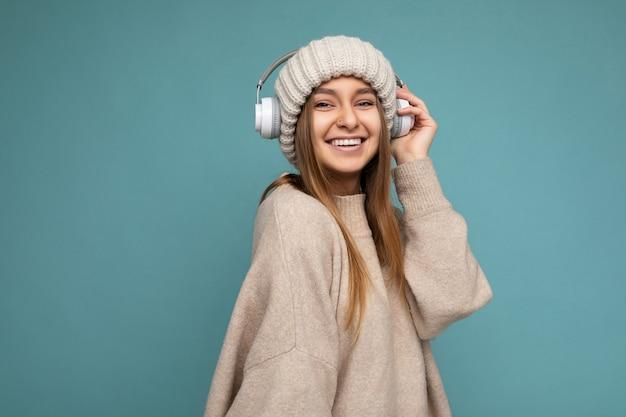 Giovane donna bionda sorridente positiva attraente che porta maglione e cappello beige di inverno