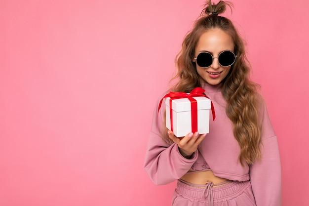 Attraente giovane donna riccia bionda positiva isolata su pink