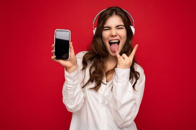 Attraente giovane donna riccia bruna positiva che indossa una camicia bianca isolata su sfondo rosso wall