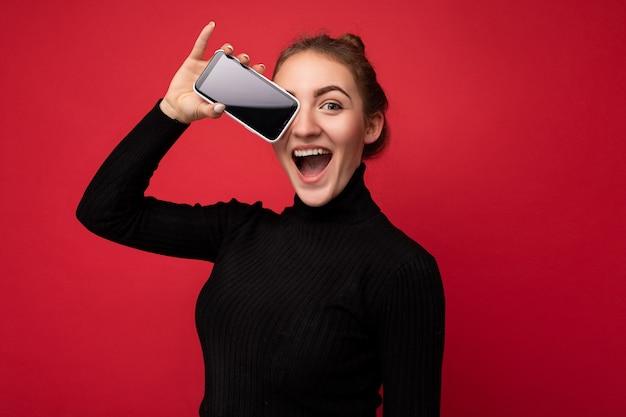 Attraente giovane donna bruna positiva che indossa un maglione nero