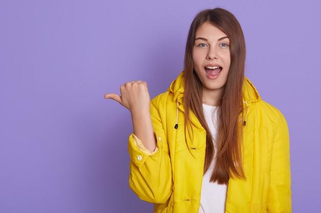 Attraente giovane donna positiva con i capelli lunghi che punta con il pollice lontano, indicando lo spazio della copia sul muro bianco, con uno sguardo gioioso e felice