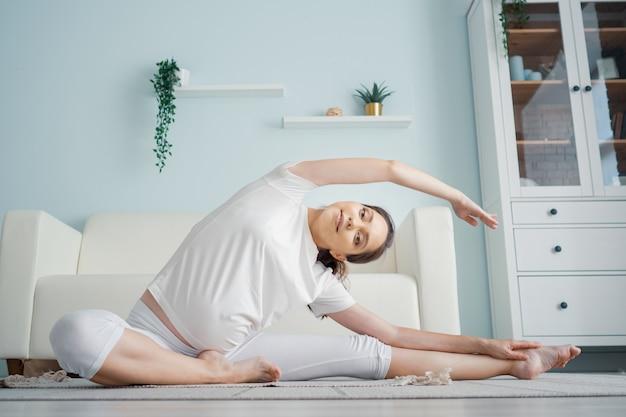Attraente signora incinta in abiti bianchi fa posizione janu sirsasana seduta sul pavimento con tappeto contro il divano di design in una spaziosa stanza a casa