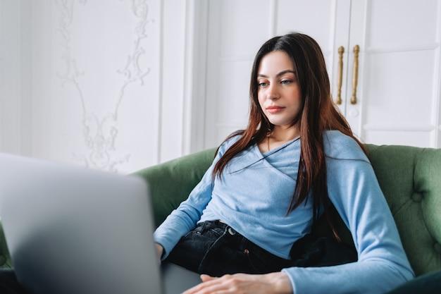 Attraente piuttosto giovane donna in occhiali freelance utilizzando il computer portatile in ufficio a casa, digitando il testo.