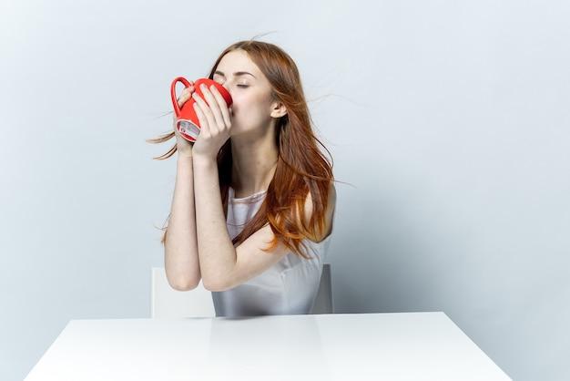 Attraente donna dai capelli rossi che beve da una tazza rossa mentre