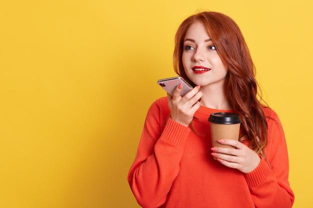Attraente donna dai capelli rossi che registra i messaggi vocali