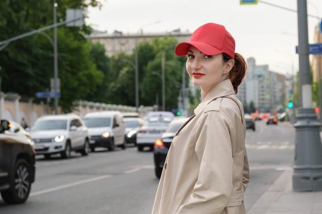 Attraente giovane donna dai capelli rossi con un berretto da baseball rosso e un impermeabile beige si trova sul lato di una strada cittadina. in giro per la città.