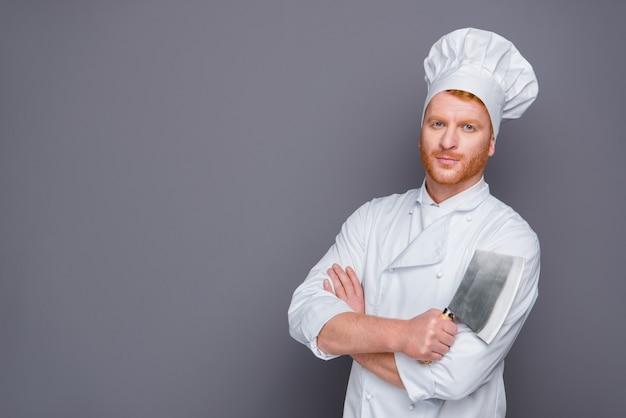 Cuoco unico attraente della testarossa che posa nella sua uniforme